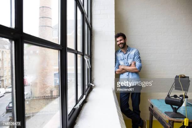 smiling man leaning against a wall in his loft - appoggiarsi foto e immagini stock