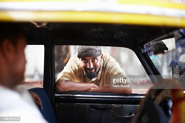 smiling man leaning in taxi cab window - mumbai stock-fotos und bilder