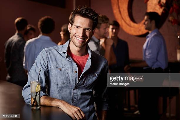 Smiling man leaning on counter in nightclub