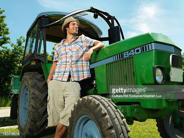Smiling man leaning on tractor