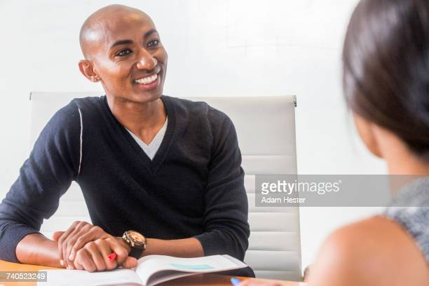 smiling man listening in meeting - non binary gender stock pictures, royalty-free photos & images