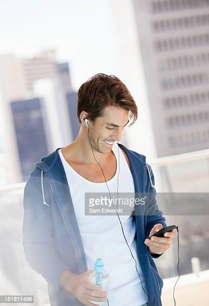 Homme souriant écoute pour lecteur mp3 sur la ville, balcon