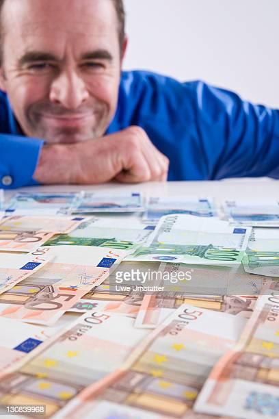 Smiling man looking a bank notes