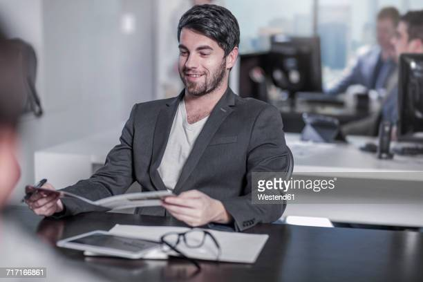 Smiling man looking at booklet at desk in city office