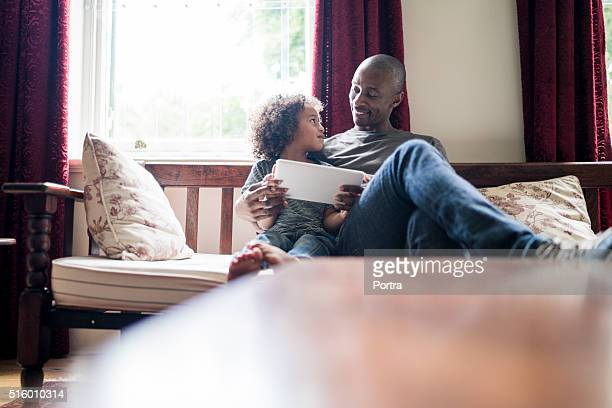 Smiling man looking at daughter using digital tablet on sofa