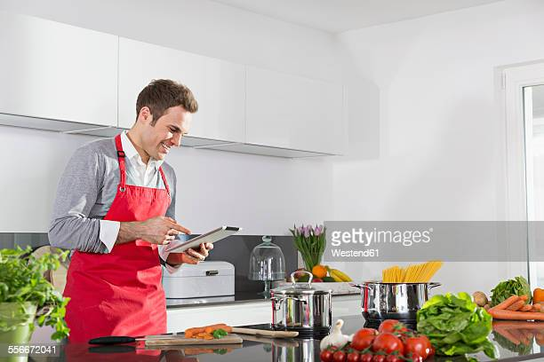 Smiling man looking at digital tablet in the kitchen
