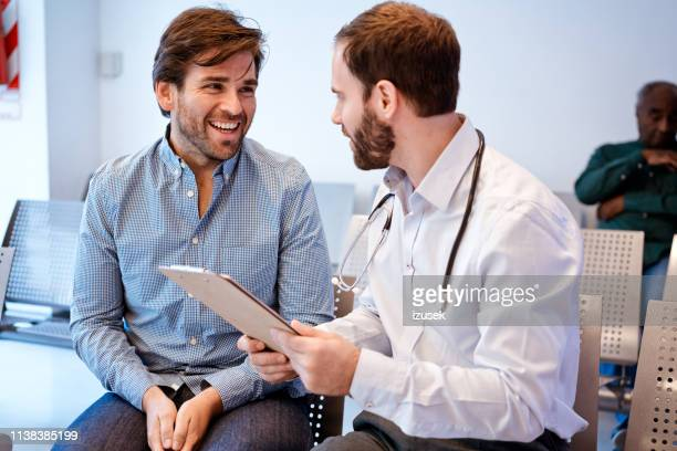 smiling man looking at doctor with clipboard - outpatient care stock pictures, royalty-free photos & images