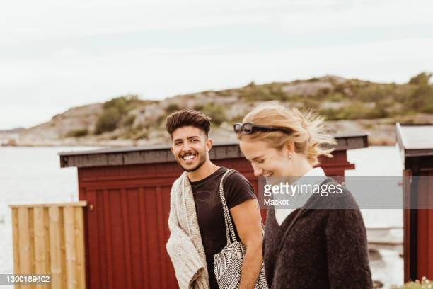 smiling man looking at female friend while standing against sky at harbor - sweden stock pictures, royalty-free photos & images