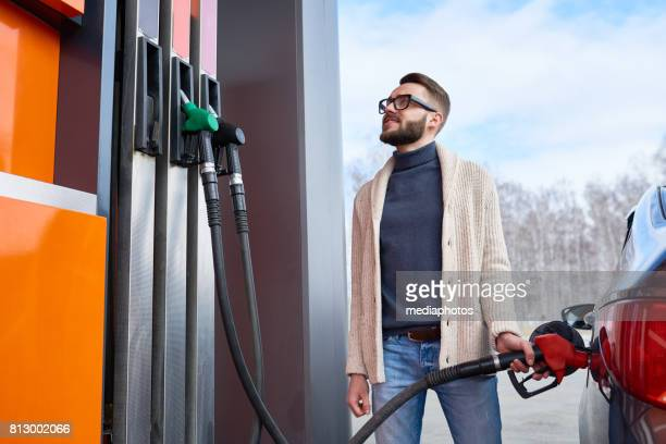 smiling man looking at fuel meter at gas station - refuelling stock pictures, royalty-free photos & images