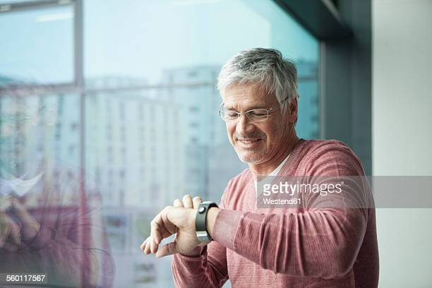 Smiling man looking at his smartwatch