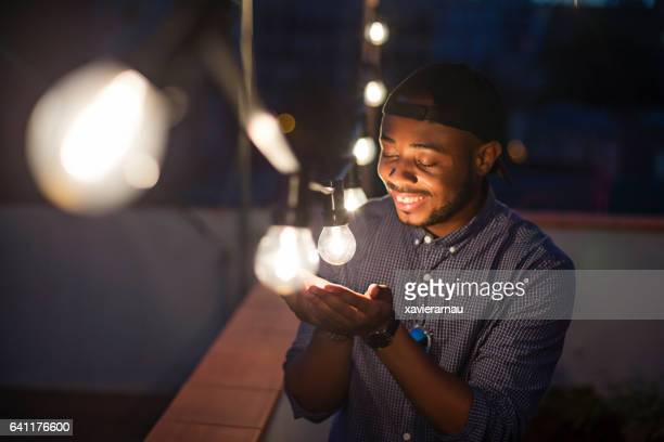 Smiling man looking at light bulb during terrace party