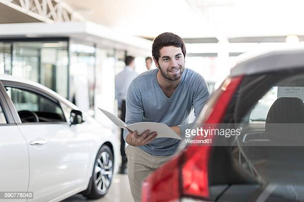 Smiling man looking at new car at car dealership