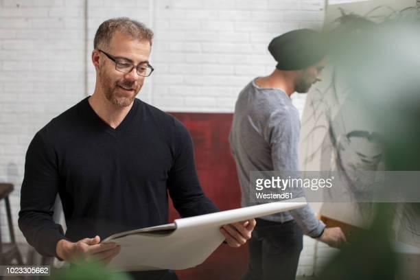 smiling man looking at sketchbook in artist's studio - kunsthändler stock-fotos und bilder