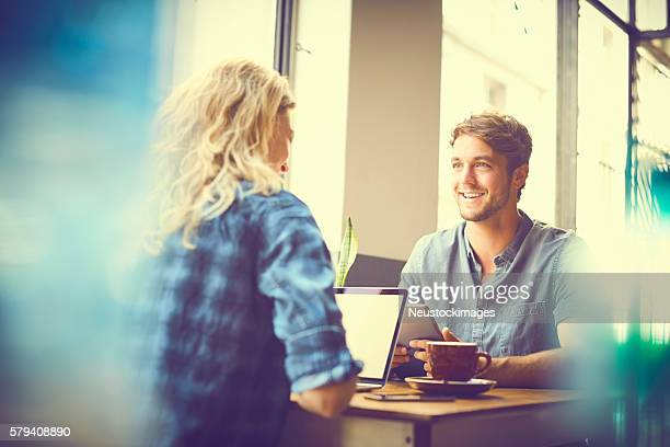 Smiling man looking at woman at table in cafe