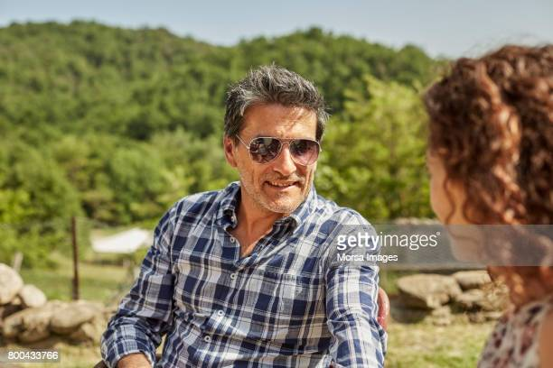 Smiling man looking at woman while sitting in yard