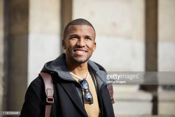 homme de sourire regardant loin dans la ville le jour ensoleillé - 25 29 ans photos et images de collection