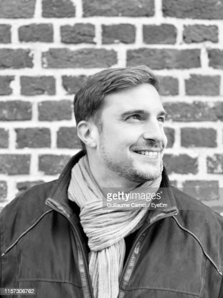 smiling man looking away while standing against wall - carnet stock photos and pictures