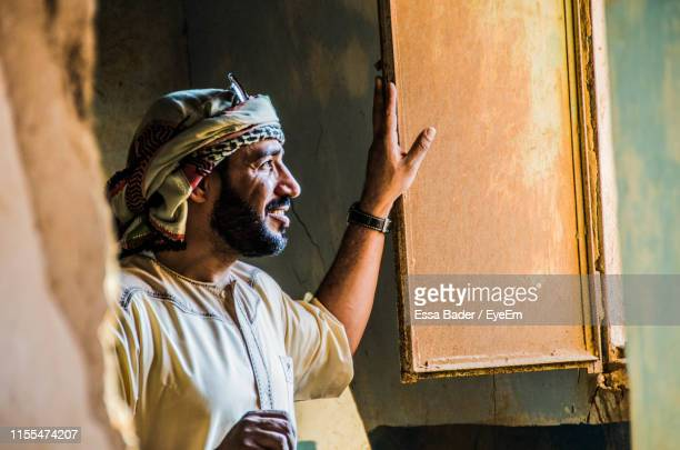 smiling man looking away while standing by window of abandoned house - saudi arabia stock pictures, royalty-free photos & images