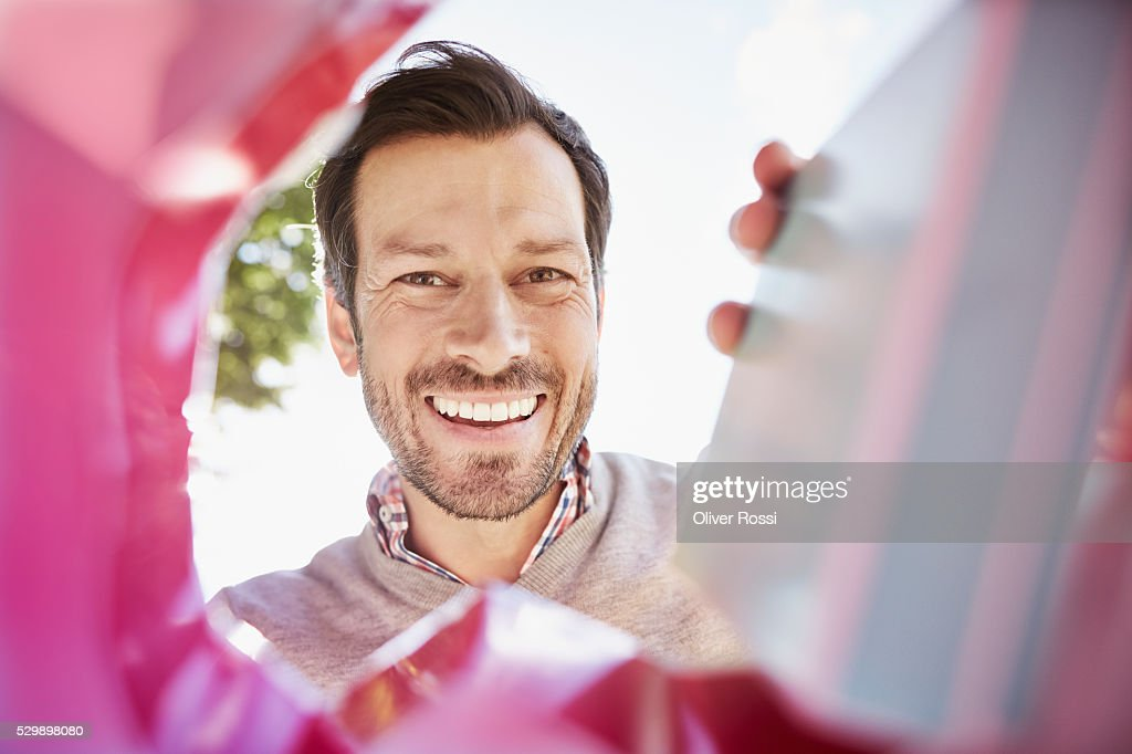 Smiling man looking into shopping bag : ストックフォト