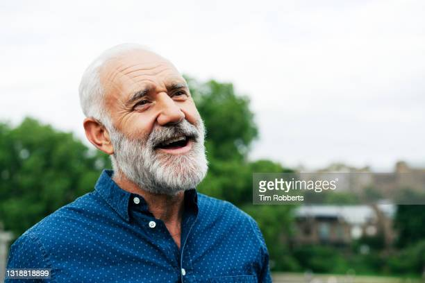 smiling man looking up - mature men stock pictures, royalty-free photos & images