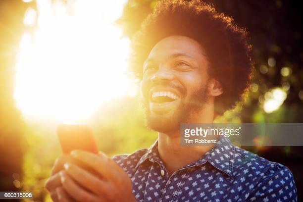 Smiling man looking up with smart phone