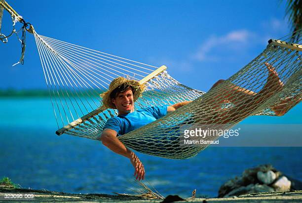 Smiling man lying in hammock,with sea in background