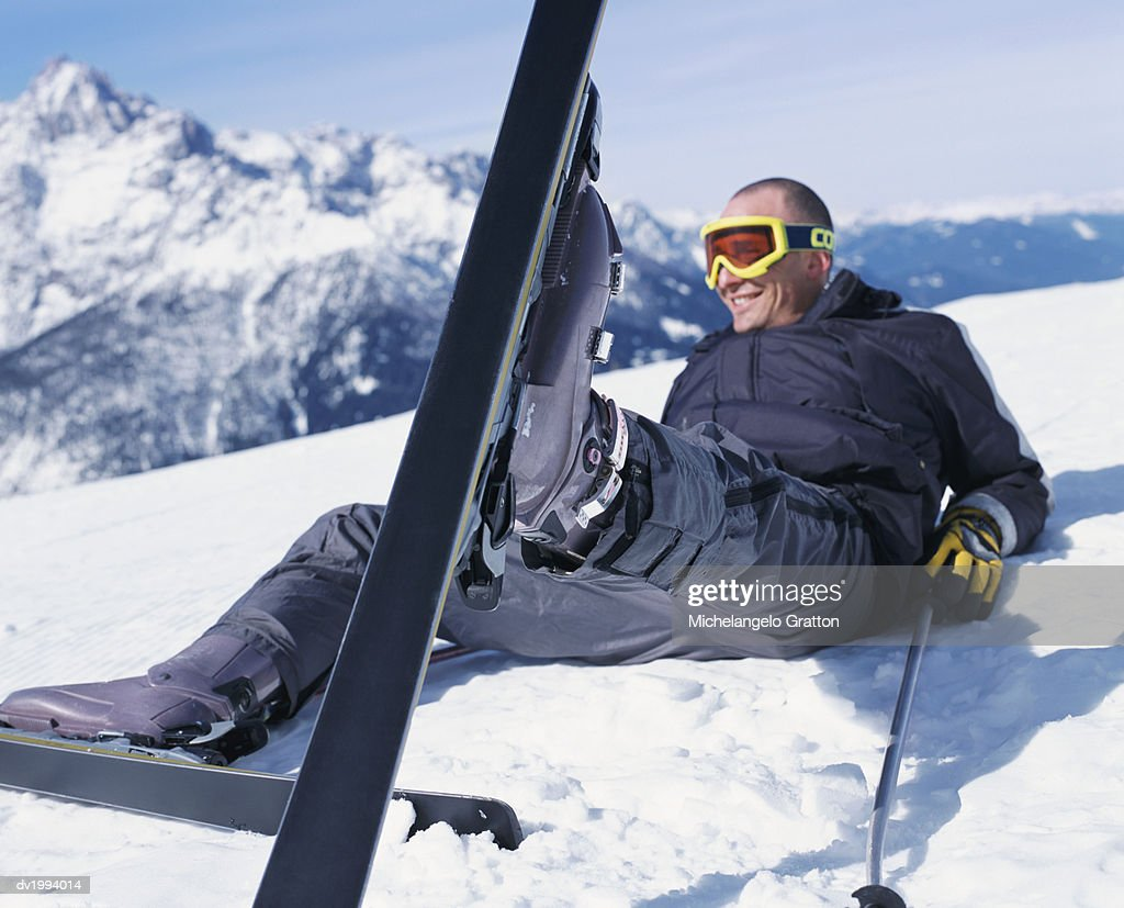 Smiling Man Lying in the Snow With His Skis on a Slope : Stock Photo