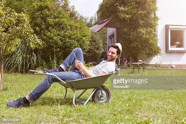 Smiling man lying in wheelbarrow in garden