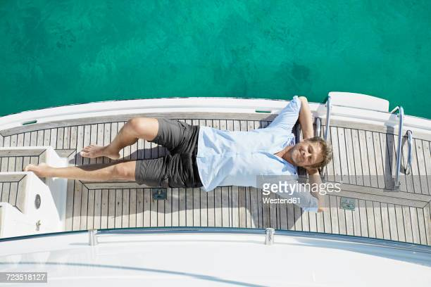 Smiling man lying on deck of his motor yacht