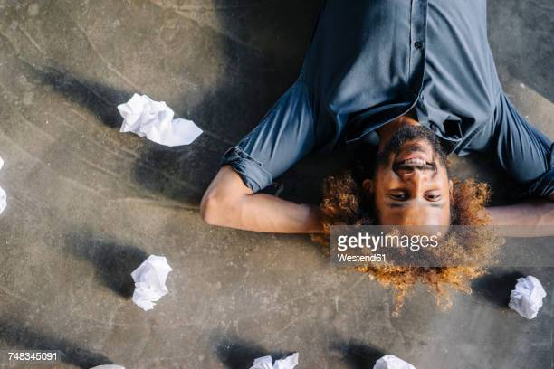 Smiling man lying on the floor surrounded by crumpled paper