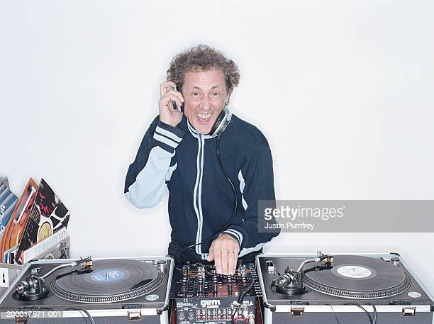 smiling man mixing records on turntable, portrait - dj stock pictures, royalty-free photos & images