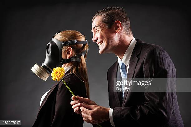 Smiling man offers woman in gas mask a flower