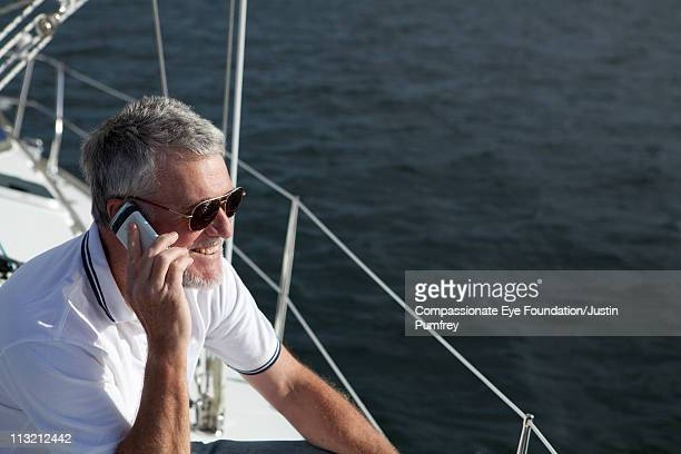 Smiling man on a boat talking on cell phone