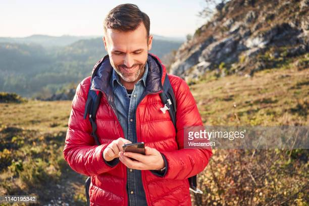 smiling man on a hiking trip in the mountains checking cell phone - red jacket stock pictures, royalty-free photos & images