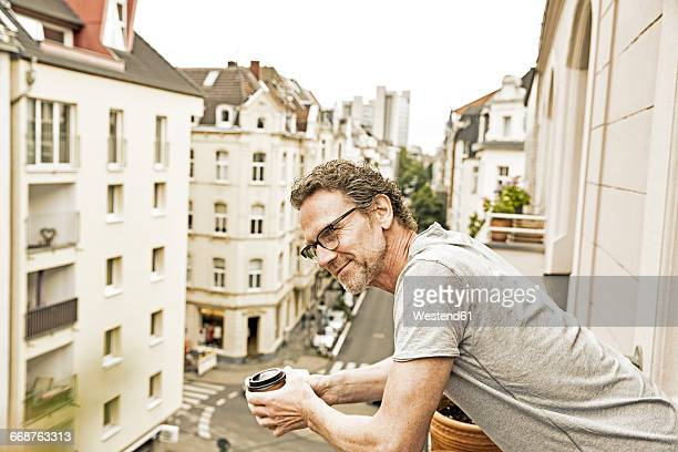 Smiling man on balcony looking down
