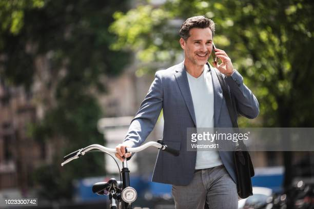smiling man on cell phone pushing bike in the city - ジャケット ストックフォトと画像