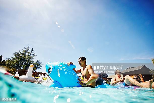 smiling man on inflatable toy in outdoor pool - inflatable stock pictures, royalty-free photos & images