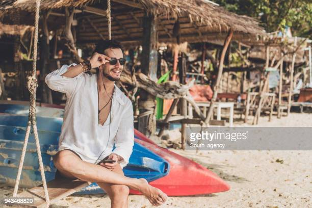 smiling man on swing - muscle men at beach stock photos and pictures