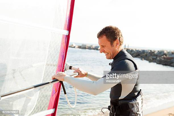 smiling man on the beach holding surfboard - windsurfing stock pictures, royalty-free photos & images