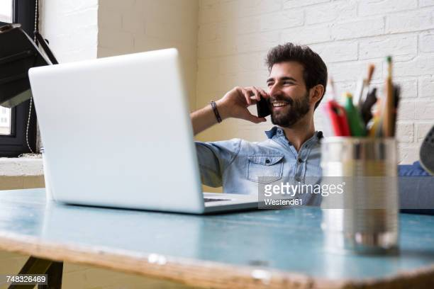 Smiling man on the phone sitting at desk in his loft