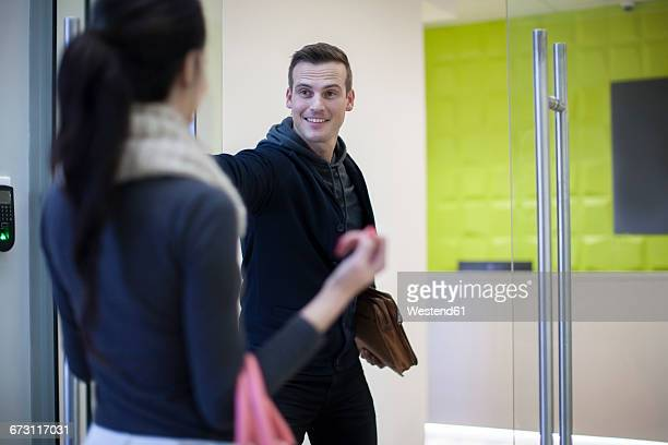 Smiling man opening door for young woman