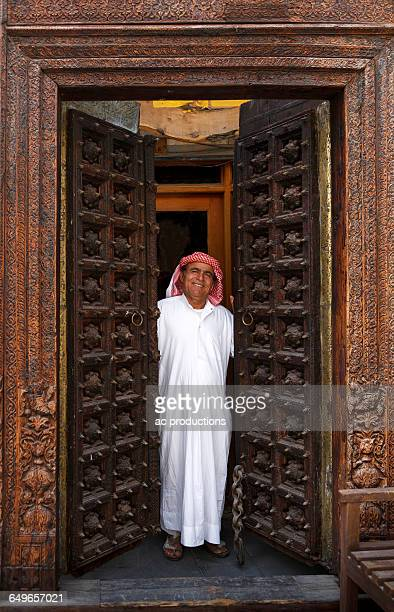 smiling man opening ornate doors - doha stockfoto's en -beelden