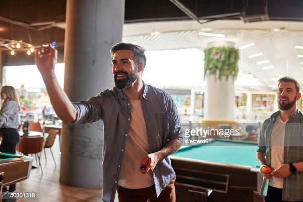 smiling man playing darts - darts stockfoto's en -beelden