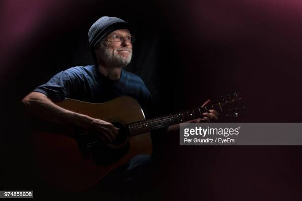 Smiling Man Playing Guitar In Darkroom