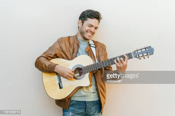 smiling man playing guitar in front of a wall - guitarist stock pictures, royalty-free photos & images