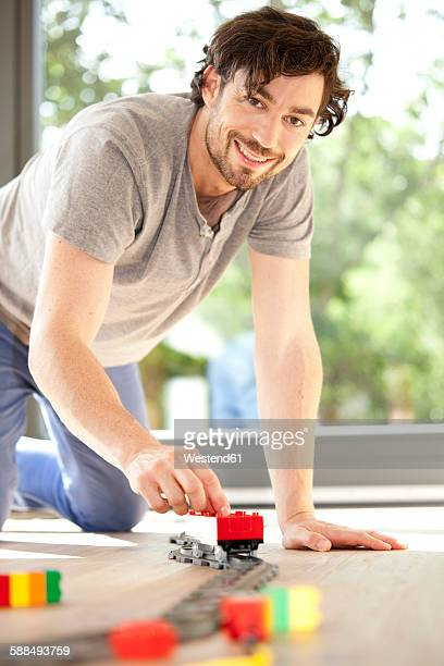 Smiling man playing with toy train