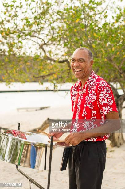 smiling man plays steel drum on the beach - steel drum stock photos and pictures