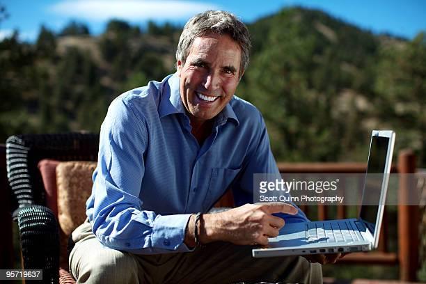 Smiling man pointing at laptop