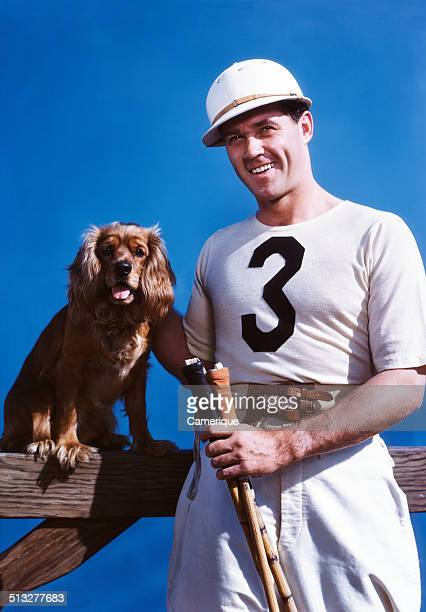 Smiling man polo player posing with cocker spaniel dog Los Angeles California 1949