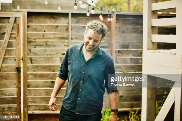 smiling man preparing barbecue before party with friends on summer evening - stubble stock pictures, royalty-free photos & images